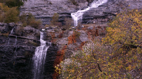 Panning shot of a waterfall with autumn foliage seen in the foreground Footage