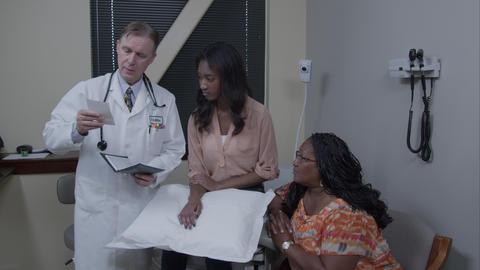 Doctor giving patient's mother a prescription Live Action