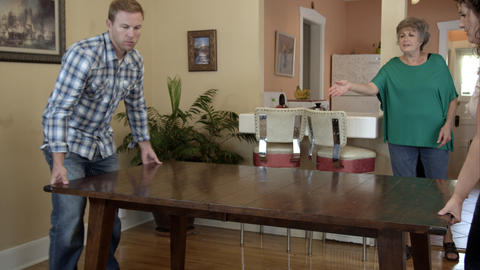 Young man and woman moving table for elderly woman Live Action
