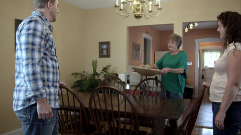 Elderly lady adorning dining room table with young man and woman Footage