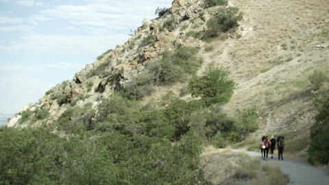 Wide shot of four people hiking on a gravel trail beside a desert mountain Footage