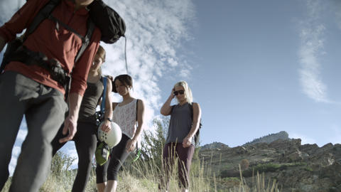 Four people hiking down a mountain trail toward the camera Footage