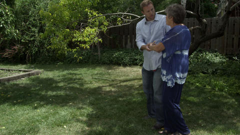 Elderly woman walking with man in backyard. Man catches her when she stumbles Footage