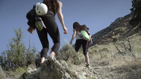 Three women and man hiking up a desert mountain trail, carrying climbing gear Footage