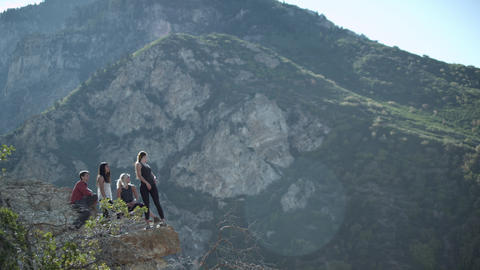 Four people on a mountain rock outcropping admiring the view Footage