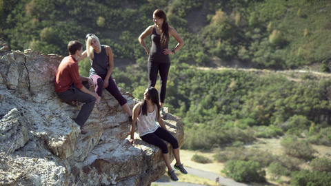 Shot from above of four people on a rock outcropping with a high five Footage