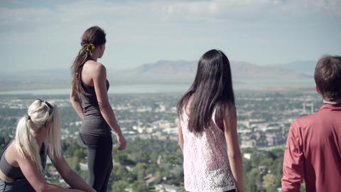 Four poeple admiring the view overlooking a city and lake Footage