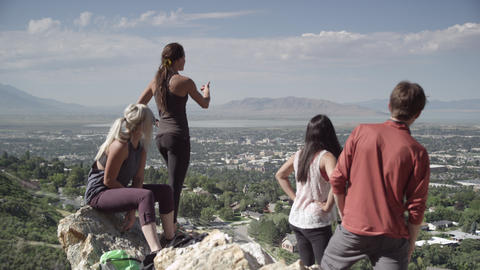 Four poeple looking at the view overlooking a city and lake Footage