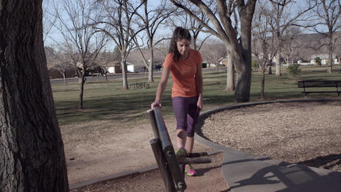 Woman wearing athletic clothing stretching in the park Footage