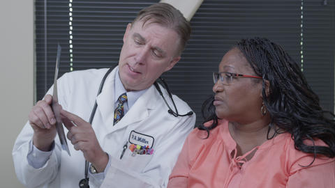 Doctor explaining x-ray to woman Footage
