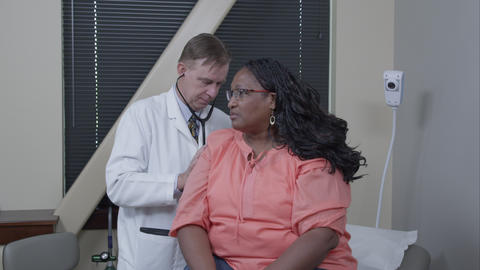 Doctor examining woman's breathing and heart rate Live Action