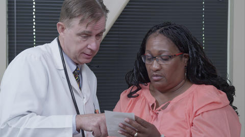 Doctor giving and explaining prescription to woman Footage