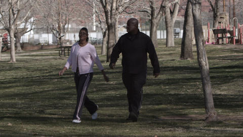 Couple in athletic clothing walking through the park Live Action