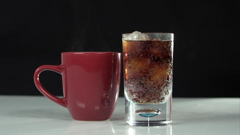 Steaming mug next to glass of soda Footage