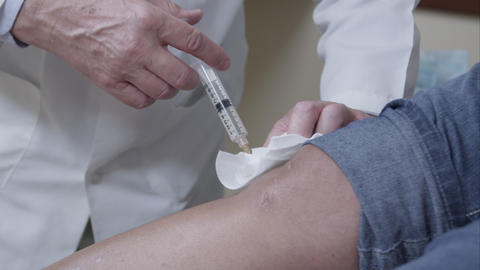 Tight shot of doctor making injection to patient's knee Footage
