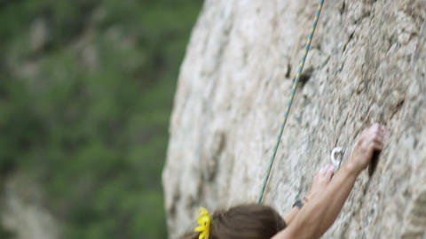 Rock climbing woman, with dreads, nearing her friends at the top Footage