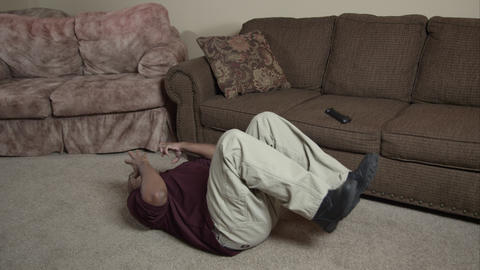 Man watching TV on couch falls off and family rushes to help Footage