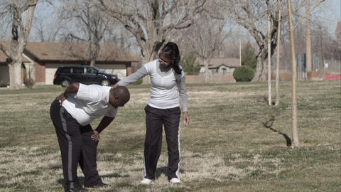 Man bending over with back pain in the park with his wife Live Action