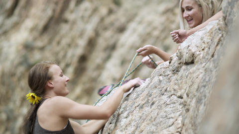 Rock climbing woman, helped to the top by her friends Footage