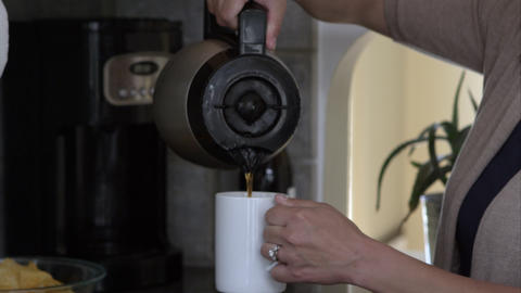 Tight shot of a woman pouring coffee into mug in the kitchen Footage
