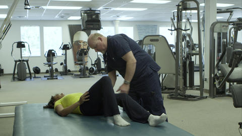 Physical therapist working with woman's leg Live Action