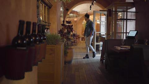 Modern restaurant interior. Tall bearded stylish man opening the door and Archivo