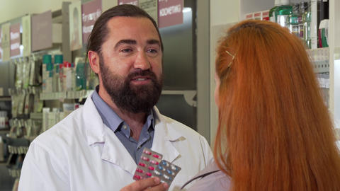 Friendly male pharmacist selling pills to female customer Footage
