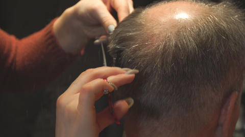 Woman hairdresser cuts a man with receding hairline with scissors Archivo