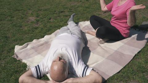 Senior couple enjoy sun rays at green meadow Footage
