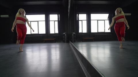 Sexy blond girl dances in the studio near mirror Footage