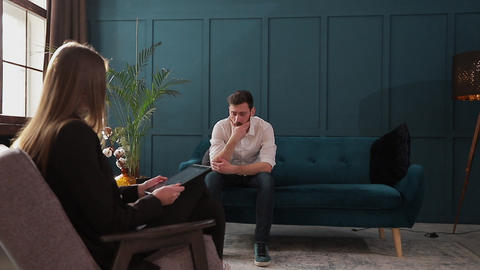 Man client sitting with female psychologist on the comfortable couch during the Footage