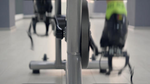 Close up legs spinning pedals on static bike at cycling class in gym, back view Live Action