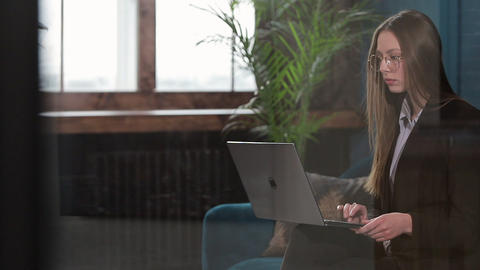 Portrait of an elegant businesswoman sitting with laptop on the couch at the Footage