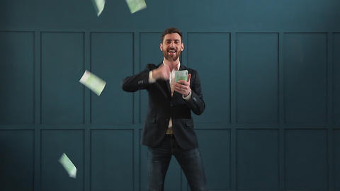 Young happy businessman dancing and throwing money. Slow motion. Successful Live Action