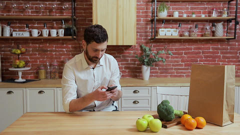 Man browsing on mobile phone at home kitchen. Handsome young man browsing on Footage