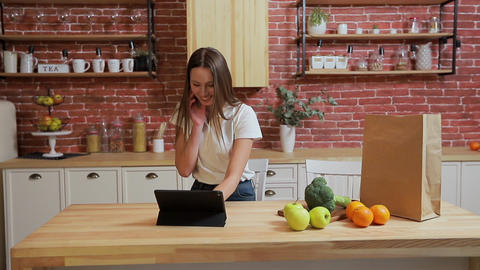 Woman browsing on tablet PC at home kitchen. Young woman browsing on Tablet PC Live Action