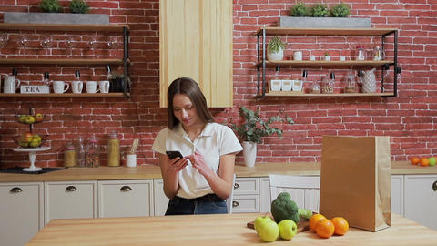 Woman browsing on mobile phone at home kitchen. Young woman browsing on Footage