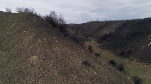 Flight through hilly landscape. Burnt grass. Camera ascendingm reveals landscape GIF