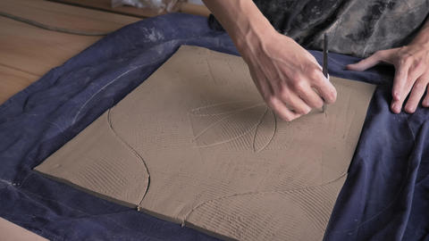 ceramist creates a pattern and relief dolly shot Live Action