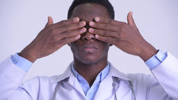 Face of young African man doctor showing see no evil concept Footage