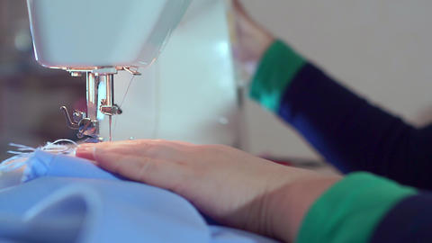 The hand of the seamstress lowers the needle of the sewing machine. She is Live Action
