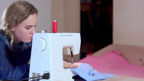 A young seamstress sews clothes on a sewing machine. Slow motion, camera slide Live Action