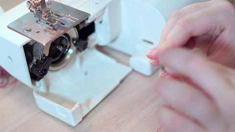 Close-up, seamstress hands put a bobbin with thread in the sewing machine. Slow Footage