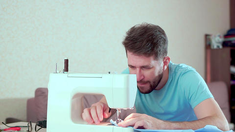 A man runs a sewing machine. Workplace at home Live Action