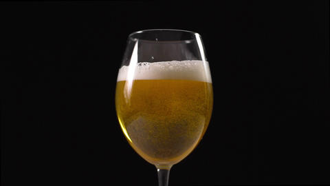 Golden foamy beer is poured to the glass in slow motion, beer glass in dark Live Action