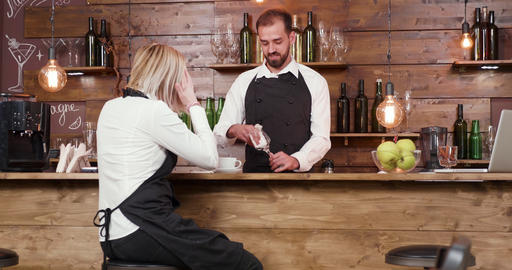 Waitress at a bar counter passionately telling a story to the bartender Live Action