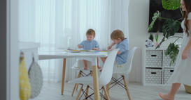 Young Mom and two sons 2-4 years old draw pencils drawing on boomega sitting at Footage