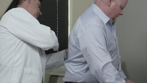 Doctor checking man's reaction to tapping on back ビデオ