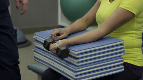 Therapist working with woman on wrist exercises Footage