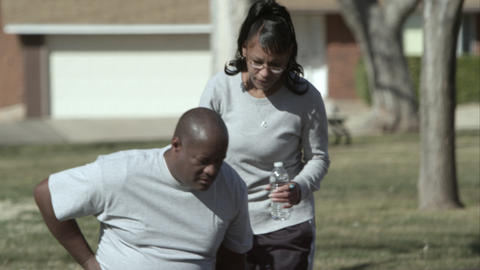 Tight shot of a man and woman walking through the park as he gets abdominal pain Live Action